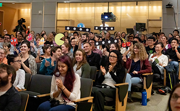 Audience for 2019 Postdoc Slam cheers finalists on.