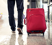 Person wheeling red luggage