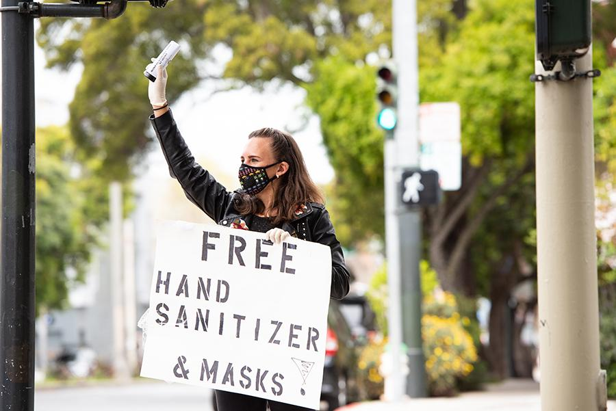 UCSF Postdoc Larissa Maier handing out free bottles of hand sanitizer and masks