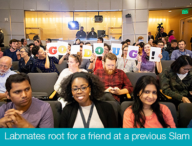 audience holds up sign at previous postdoc slam event